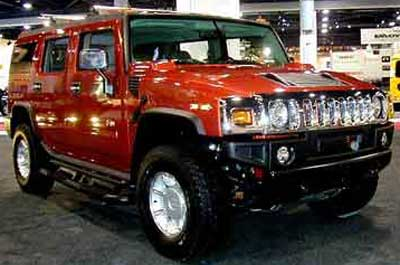 Chauffeur driven burnt orange Baby Hummer H2 hire in Liverpool, Manchester, Bolton, Warrington, North West